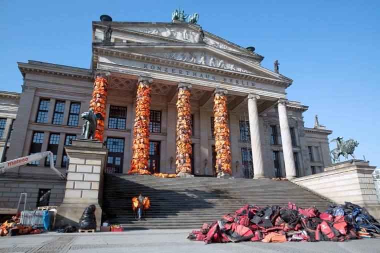 epa05158089 A general view shows workers attaching life vests to the Berlin's concert hall as part of an art action in Berlin, Germany, 13 February 2016. Chinese artist Ai Weiwei wants to draw attention to the fate of many refugees who have drowned on their way to Europe. Weiwei got the life vests from the Greek island of Lesbos.   EPA/JOERG CARSTENSEN