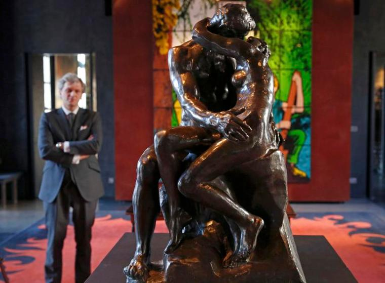 """Auctioneer Alexandre Giquello looks at the sculpture """"Le Baiser"""" (the Kiss), bronze cast made in 1927, which is part of an exceptional sale of five remarkable bronzes by the French sculptor Auguste Rodin (1840-1917), displayed in Paris, France, February 11, 2016. Five small bronze statues of French 19th century sculptor Auguste Rodin will be auctioned in Paris next week, including a cast of his famous """"The Kiss"""", which is estimated to go for at least 1.5 million euros. The five statues, which will be auctioned at auction house Drouot on Tuesday, come from the collection of late French art dealer Jean de Ruaz and have owned by his family since after World War II.   REUTERS/Philippe Wojazer"""