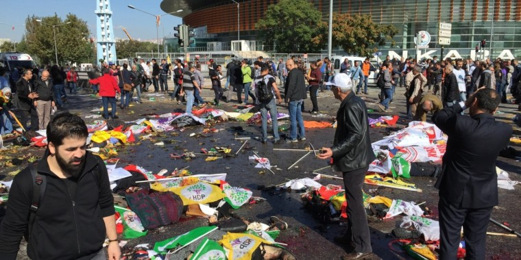 ANKARA, TURKEY: People are seen at the site of an explosion close to Ankara's main train station on October 10, 2015 in Ankara, Turkey. An explosion hit Ankara train station Saturday morning leaving dozens of people dead and injured, as many people gathered outside the station for a demonstration to be held in nearby at Sihhiye Square. (Photo by Serhan Bascuhadar/Anadolu Agency/Getty Images)