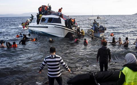 Volunteers and local residents help refugees and migrants disembark from a small vessel after their arrival in Skala Sykaminias on the northeastern Greek island of Lesbos on Friday, Oct. 30, 2015. Greek authorities say a number of people have died near other islands after two boats carrying migrants and refugees from Turkey to Greece sank overnight, in the latest deadly incident in the eastern Aegean Sea. (AP Photo/Kostis Ntantamis)
