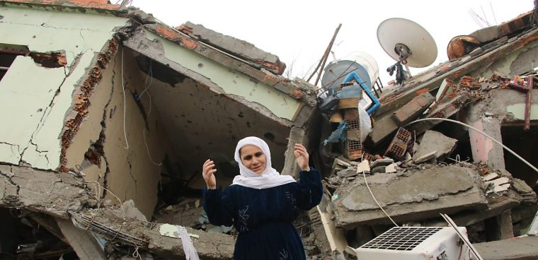 A resident gestures as she talks standing on the rubble of a destroyed house in the mostly-Kurdish town of Silopi, in southeastern Turkey, near the border with Iraq, Tuesday, Jan. 19, 2016. Turkey's prime minister announced Tuesday that military operations against Kurdish rebels have ended in one mainly Kurdish southeastern town. The military is still fighting militants linked to the Kurdistan Workers' Party, or PKK, in two other urban areas. (AP Photo/Mahmut Bozarslan)
