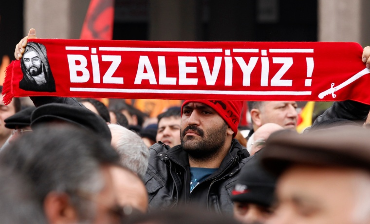 "A protester holds a banner reading ""we are alevi"" as he and many others wait to hear the decision of the court in front of a courthouse in Ankara March 13, 2012. Turkish police fired tear-gas and water cannon to disperse hundreds protesting on Tuesday against the dropping of a case against five people charged with killing 37 writers and liberals in a 1993 hotel fire set off by Islamist rioters.The opposition accused Prime Minister Tayyip Erdogan and his AK Party, which emerged from a series of banned Islamist parties of being responsible for the failure to find the five.The case against two others charged with the kilings was dropped as the accused had died. One of them, the prime suspect who was the local mayor from the same party to which Erdogan belonged, passed away last year, close to the scene of the fire. REUTERS/Umit Bektas (TURKEY - Tags: POLITICS CIVIL UNREST)"