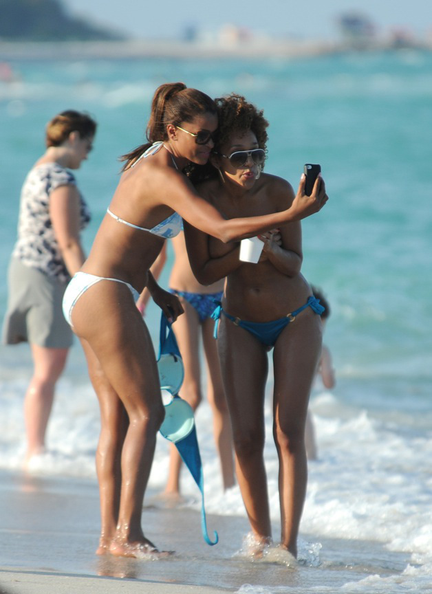 Claudia Jordan plays around and takes pictures with model friend Aisha Thalia who decides to go toploss while on the beach in Miami