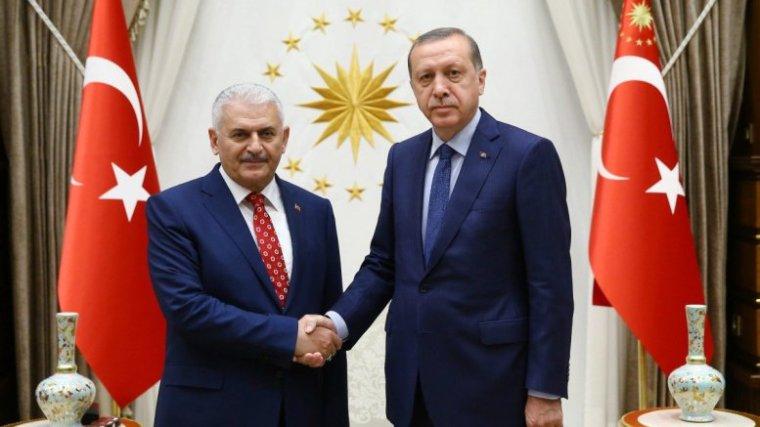 Erdogan (R) shake hands with Turkish Prime Minister Binali yildirim
