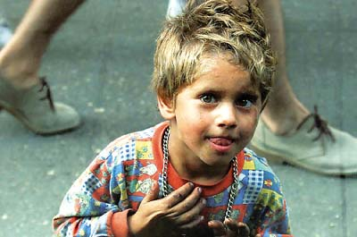 A Romanian street child peers through a food shop window in Bucharest August 7, 2000 as he begs outside for small change. Romania, which has the highest infant death rate in Europe, issued recently a set of rules for child protection, descentralised administration and finance child care institutions as well as improved protection for abandoned children and street children. Some 100,000 abandoned children are locked in badly-managed state institutions inherited from the former communist regime. REUTERS/Radu Sigheti