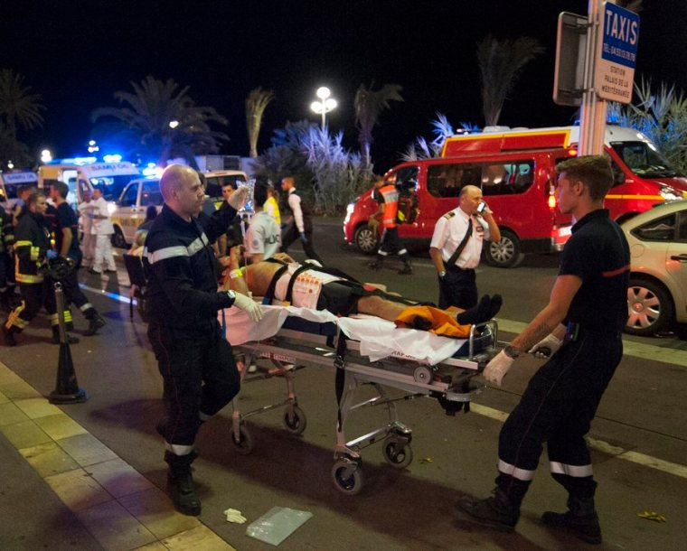epa05425177 Wounded people are evacuated by emrgency teams from the scene where a truck crashed into the crowd during the Bastille Day celebrations in Nice, France, 14 July 2016. According to reports, at least 70 people died and many were wounded after a truck drove into the crowd on the famous Promenade des Anglais during celebrations of Bastille Day. Anti-terrorism police took over the investigation in the incident, media added.  EPA/OLIVIER ANRIGO