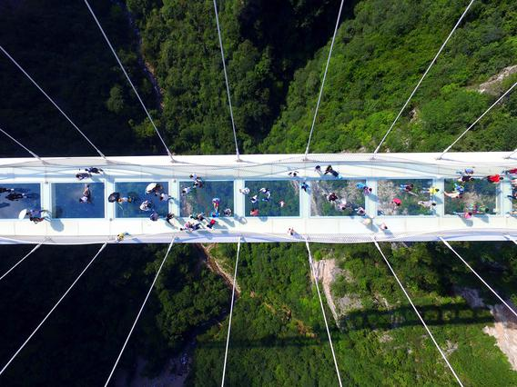 Visitors walk across a glass-floor suspension bridge in Zhangjiajie in southern China's Hunan Province Saturday, Aug. 20, 2016. The bridge, which opened to the public on a trial basis on Saturday, spans 430 meters (1,410 feet) and rises about 300 meters (984 feet) above a valley in a scenic zone, making it the world's highest and longest glass-bottomed bridge according to Chinese state media. (Chinatopix via AP)