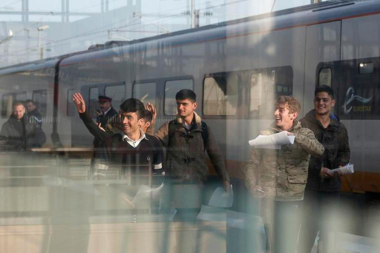 A Syrian and five Afghan boys wave on the platform of the Calais train station, northern France, as they leave for Britain.