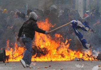 burning Greek flag