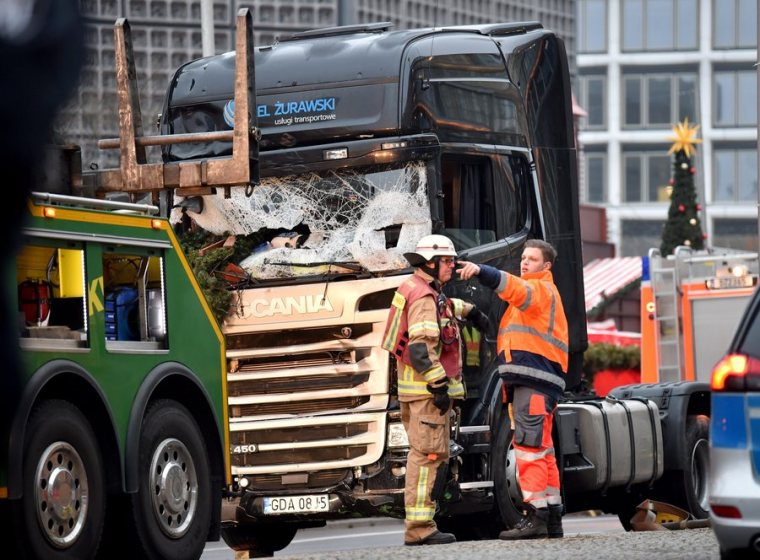 epa05683029 A firefighter and an employee of a towing company are seen near a damaged truck after it crashed into a Christmas market close to the Kaiser Wilhelm Memorial Church, in Berlin, Germany 20 December 2016. According to the police, at least 12 people were killed and at least 48 were injured after a truck ploughed into a busy Christmas market in Berlin. Authorities are investigating the incident as a 'possible terrorist attack,' media reported. EPA/BRITTA PEDERSEN