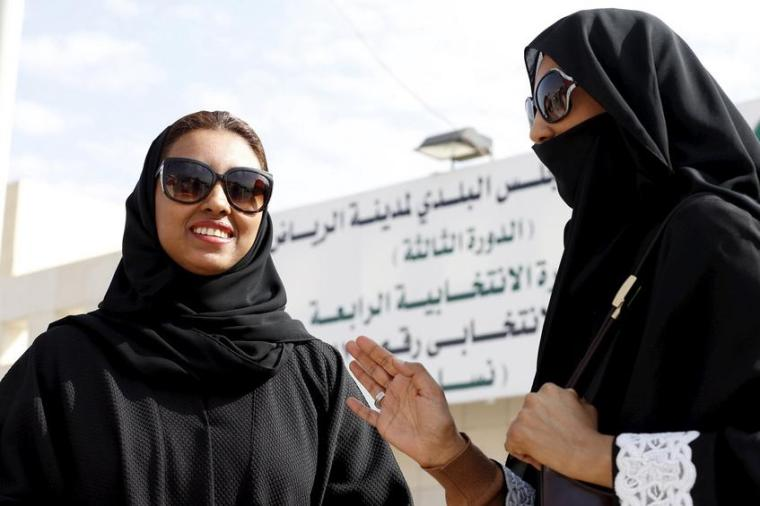 Saudi women leave a polling station after casting their votes during municipal elections, in Riyadh, Saudi Arabia.